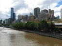 Flinders St Station by the Yarra & the business district behind it